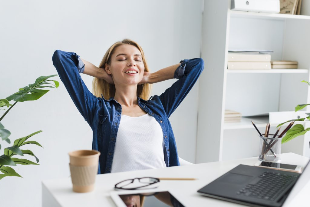 blond-woman-sitting-back-smiling-with-closed-eyes-workplace