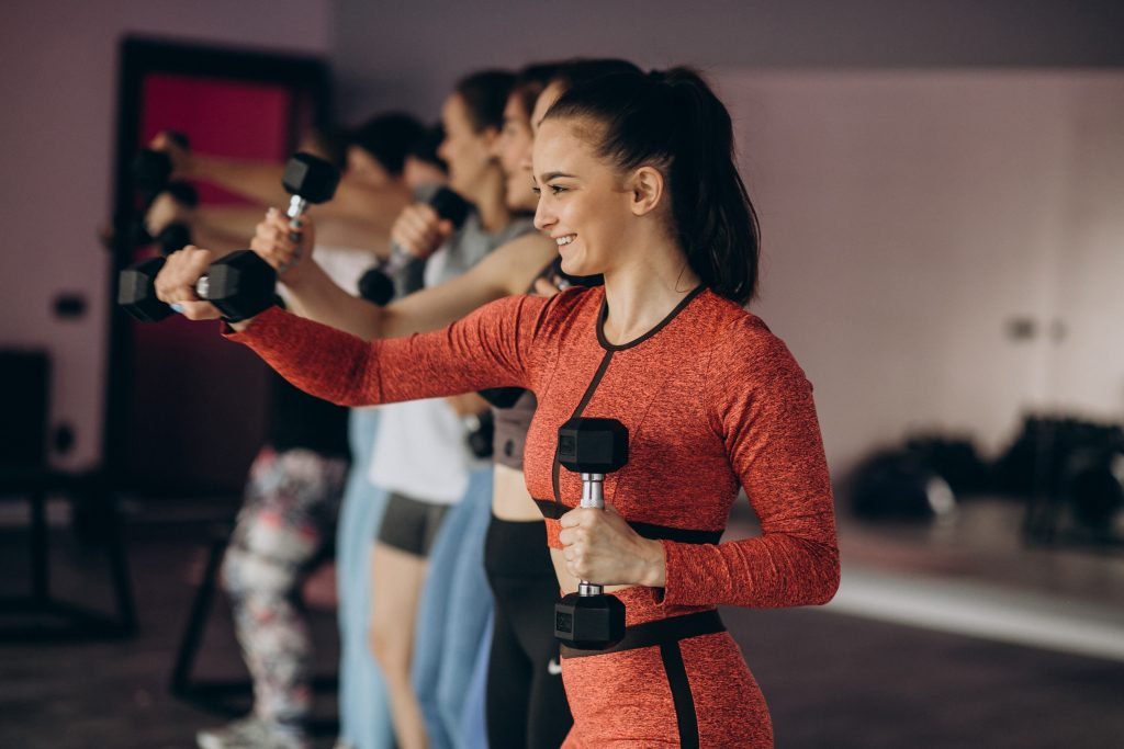 Girls team exercising aerobics together at the gym
